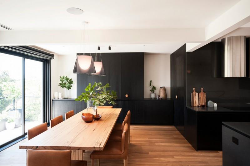 brown dining room chair wooden dining table black cabinet range hood black stovetop wooden floor pendant lamps sliding glass doors