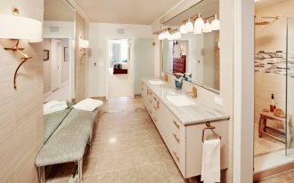 double vanity wall mirror marble top white sinks gold faucets wall sconces towel ring gold hardware grey bench beige floor tile shower head