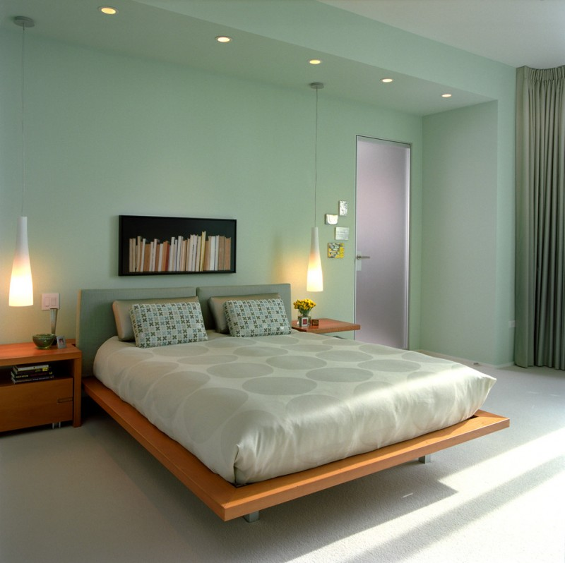 green bedroom walls artwork wooden bed green headboard silk bedding green pillows wooden nightstands pendant lamps green curtain