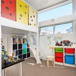 Kids White Loft Bed Colorful Border White Ceiling Fan With Light Black Table Toy Storage White Cubbies Wooden Chair Windows