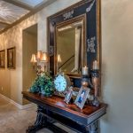 Large Ornate Mirror Black Frame Mirror Table Lamp Candle Holders Clock Frames Beige Walls Beige Floor Tile Ceiling Lamps Hallway Table
