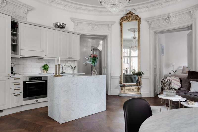 large ornate mirror white subway backsplash white cabinets shelves drawers stovetop oven white island sink countertop sofa