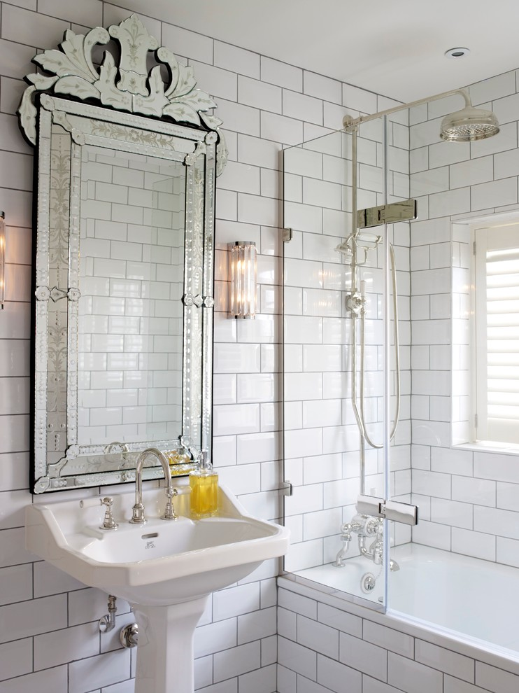 large ornate mirror white subway wall tiles white sink faucet wall sconces shower head glass shower door built in tub window