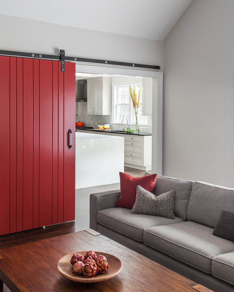 red door designs barn door grey sofa wooden table grey and red throw pillows white kitchen cabinets black granite countertop