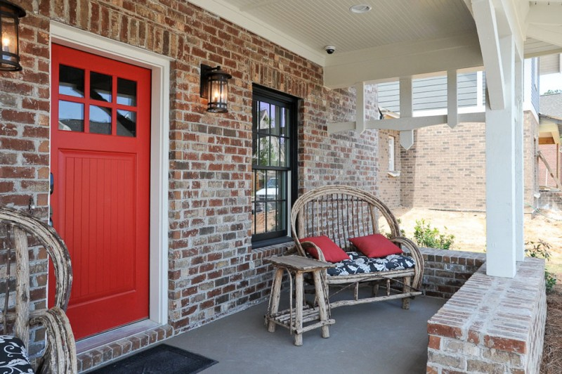 red door designs black glass wall sconces brick walls rustic wooden chair wooden side table black outdoor mat white trim ceiling