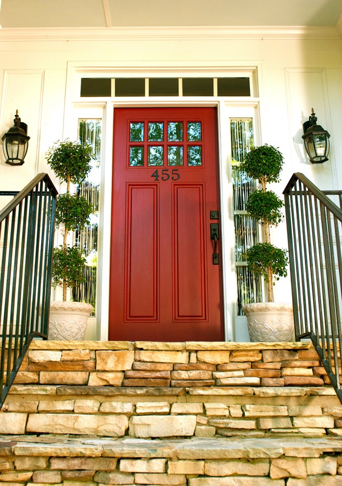 red door designs numbers wall sconces outdoor plants wooden stone stairs black iron stairs railings narrow windows