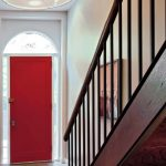 Red Door Designs Pendant Lamp Red Mediterranean Area Rug Glass Windows White Walls Artwork Wood Staircase Railing