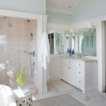 Regal Glass Glass Shower Doors White Vanity Mirror White Wall Sconces Terracotta Floor Grey Bathroom Rug Towel Hook