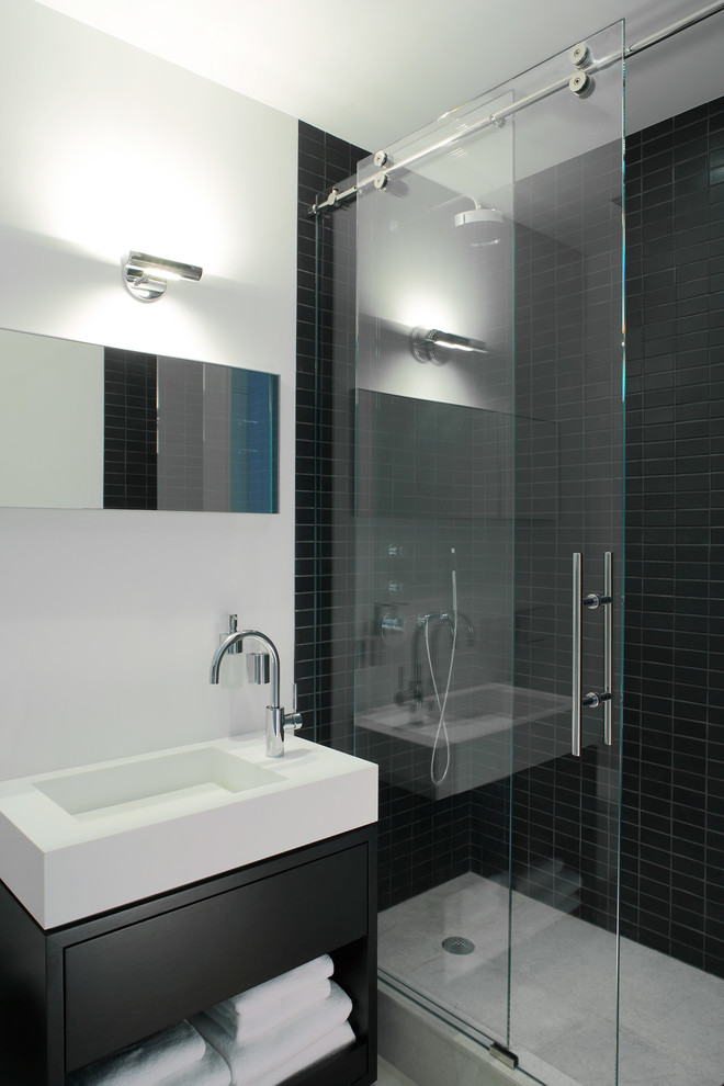 sliding glass shower door black shower tile white sink black cabinet mirror wall sconce white wall white towels