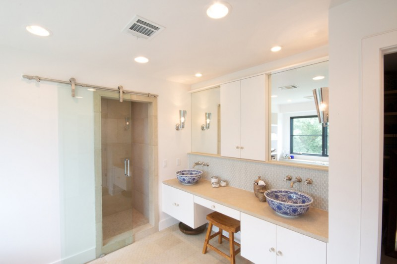 sliding glass shower door sliding glass barn door wooden stool white vanity beige countertop blue sink bowl wall mounted faucets mirrors