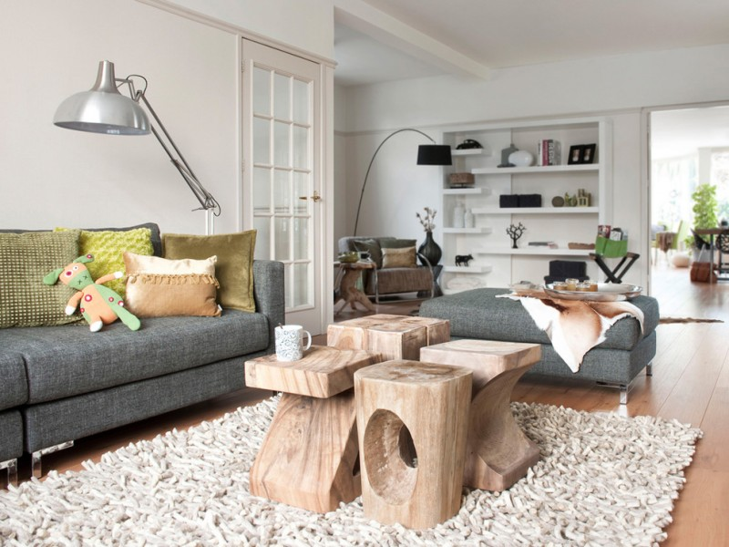 small coffee table wooden sculptural coffee table area rug dark grey sofa dark grey bench colorful pillow floor lamp