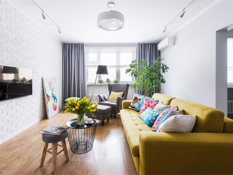 small coffee table yellow sofa colorful throw pillow wooden floor black coffee table stools grey armchair floor lamp