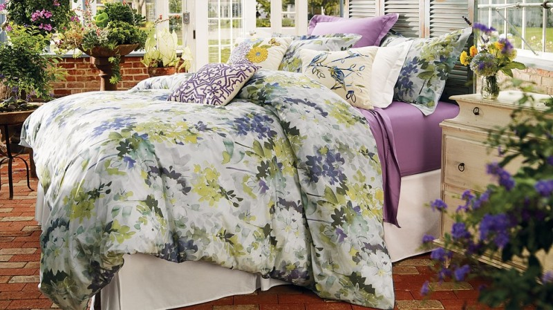 watercolor duvet floral bedding white bed rustic white nightstands brick floor indoor plants headboard glass windows