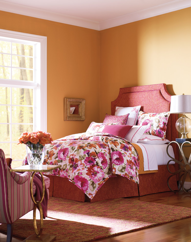 watercolor duvet orange walls pink bed pink headboard pink white pillows glass vase striped pink chairs table lamp window