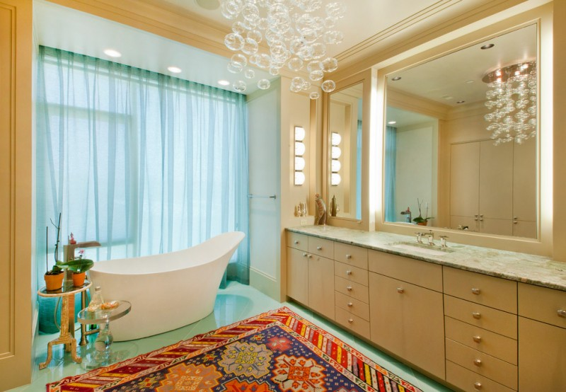 acrylic freestanding bathtub glass chandelier blue curtain colorful rug wooden vanity mirror granite countertop wall sconce