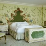 Antique Queen Bed Green Patterned Wallpaper Green Headboard White Bedding Trunk White Nightstands Wall Sconces Green Chairs Area Rug