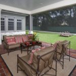 Back Lanai With Red Tiles Flooring, Brown Cushioned Sofa And Chairs, Wooden Coffee Table, Blinds