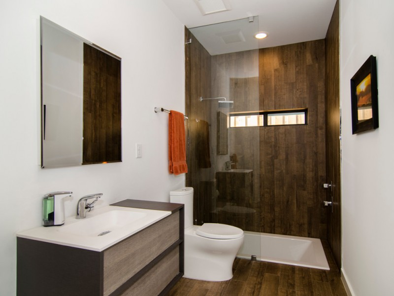 bahtroom with wooden floor, grey wooden cabinet with white marble top, white toilet, sunken bathtub in wet area with wooden wall