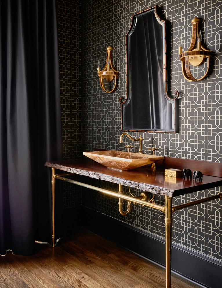 bathroom with dark wooden floor, black curtain, metallic feet table with dark stones top with brown stone sinks, mirror, wall lamp, dark wallpaper