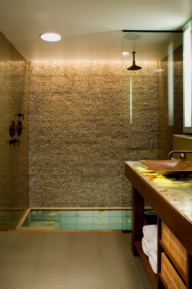 bathroom with grey flooring, stones wall in the shower area, wooden cabinet with marble top