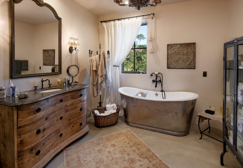 bathroom with metallic bath tub, nude flooring and wall, brown wooden cabinet with brown marble top, copper framed mirror