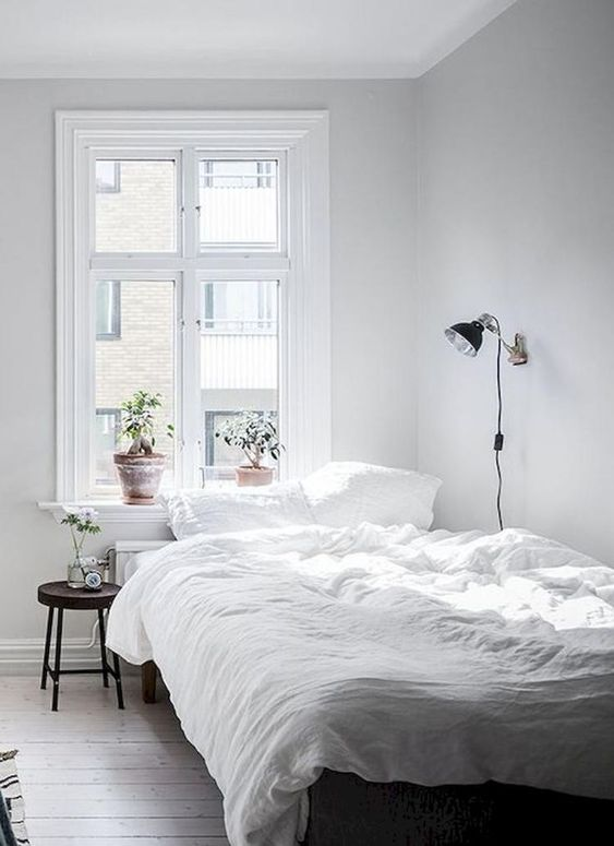 bedroom with bed wall, bed wooden flooring, black round side table, white linen bed, black wall lamp