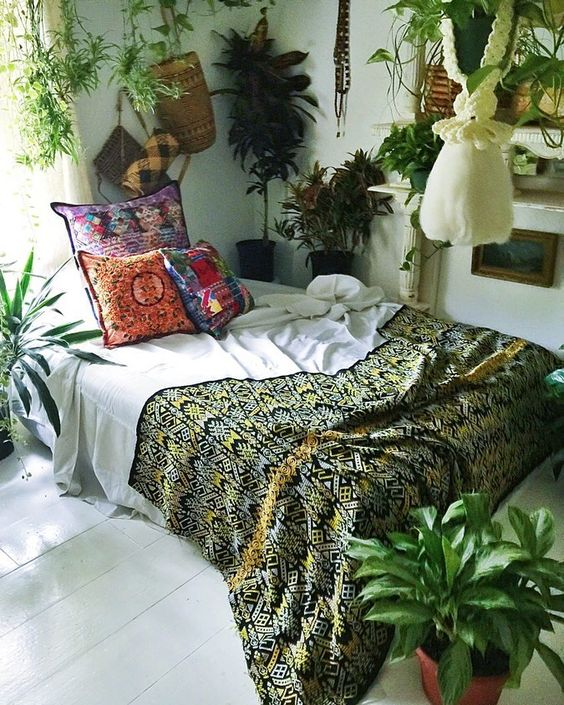 bedroom with bed without bedding, ethnic patterned pillows, plants,