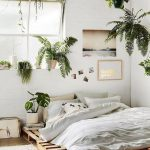 Bedroom With Brown Floor, Rug, Wooden Palette Bedding, White Bed And Pillows, Hanging Plants, Painting, Big Windows