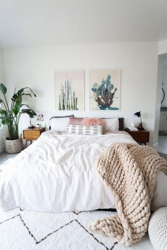 bedroom with white floor, white rug, white bed and pillows, plants, small side table, plants pictures