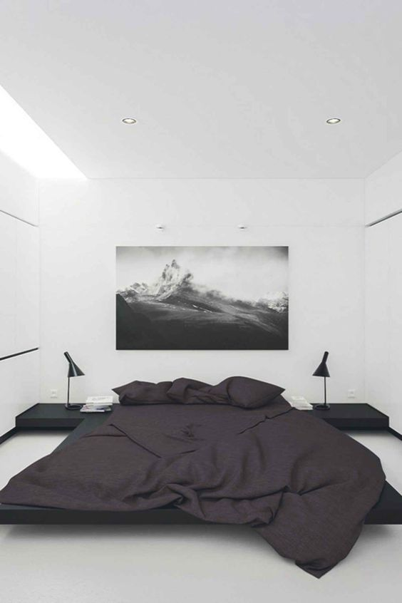 bedroom with white flooring, white wall, white ceiling, black low square side table, black table lamps, black linen bed