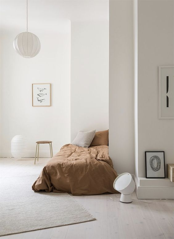 bedroom with white flooring, white wall, white hanging lamp, white nad black paintings, small bed with brown bed linen