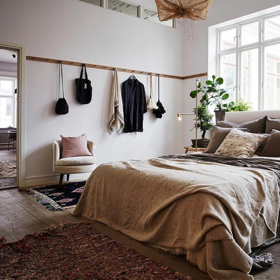 bedroom with wooden floor, rug, hanging rail, chair, simple side table, lamp, brown bed