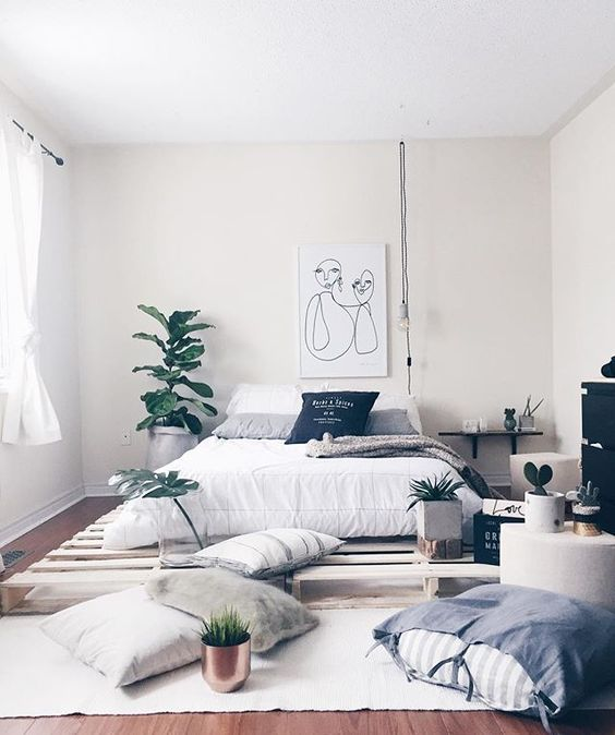 bedroom with wooden floor, wooden palette for bedding, white bed with pillows, plants, small tables, hanging shelves, black cabinet