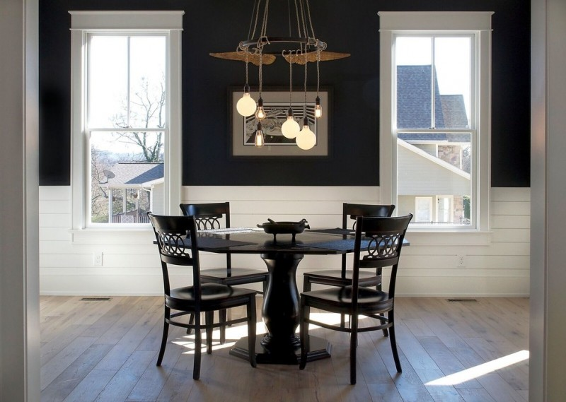black dining table wooden floor black pedestal table black dining chairs industrial chandelier white framed windows artwork black wall