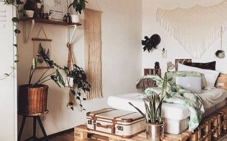 boho bedroom with wooden floor, wooden palette bedding, white bed, macrames, plants, shelves, white cupboard