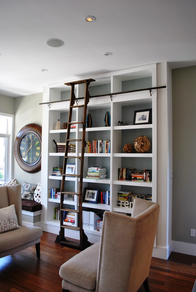 bookcase with ladder and rail beige wingback armchairs wooden floor big clock glass windows grey walls built in bookshelves