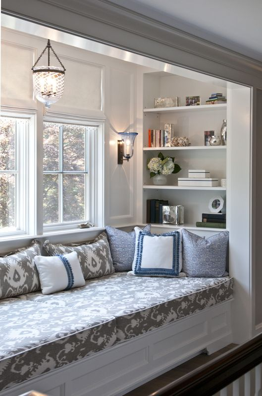 built in bed in the window sill with white wooden bedding, bookshelves inside, grey patterned cushion, ceiling lamp, wall lamp