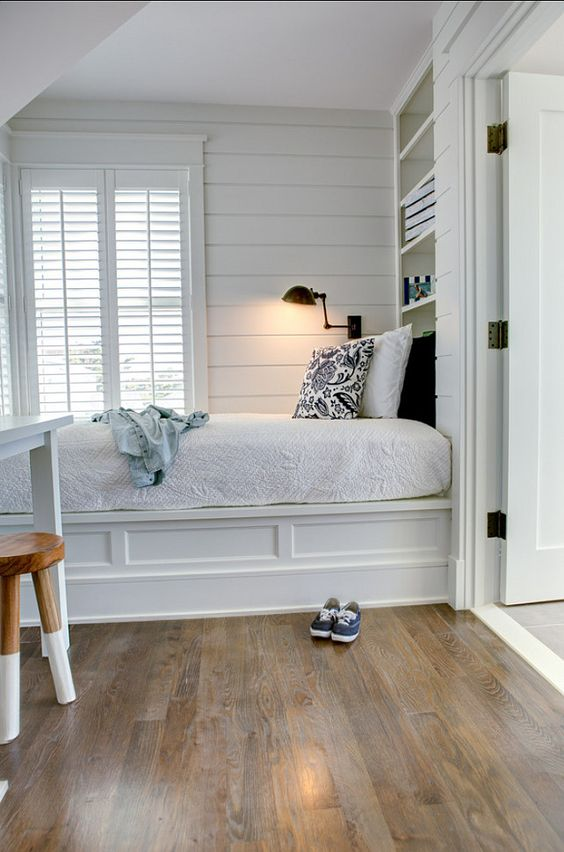 built in bed with white wooden bedding, bookshelves, bedside table,near the window