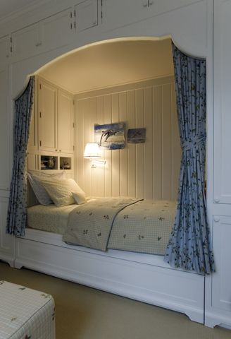 built in bed with white wooden bedding, brown linen, cabinet and shelves inside, sconces, blue curtain