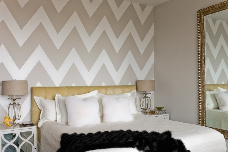 chevron accent wall big mirror with gold frame headboard mirrored nightstands table lamps white bedding white pillows black throw