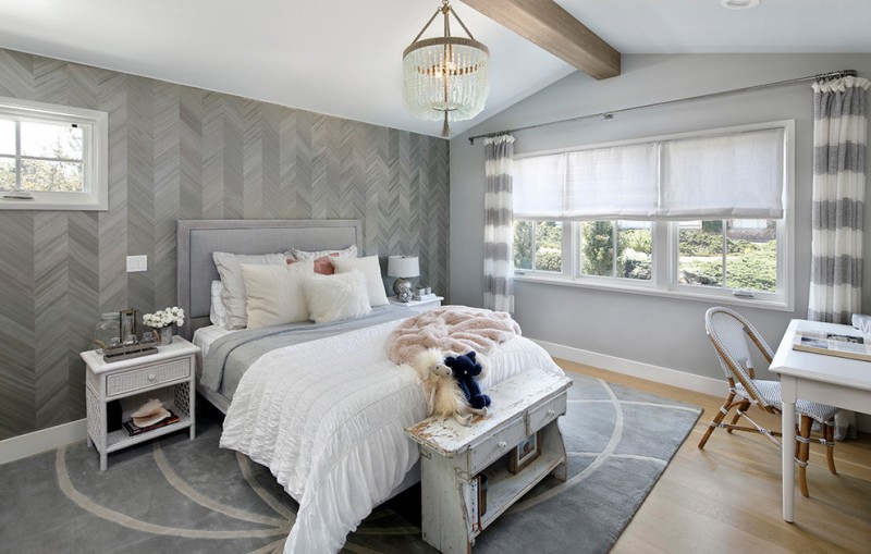 chevron accent wall grey bed headboard white nightstands chandelier table lamp white desk chair windows curtains grey rug