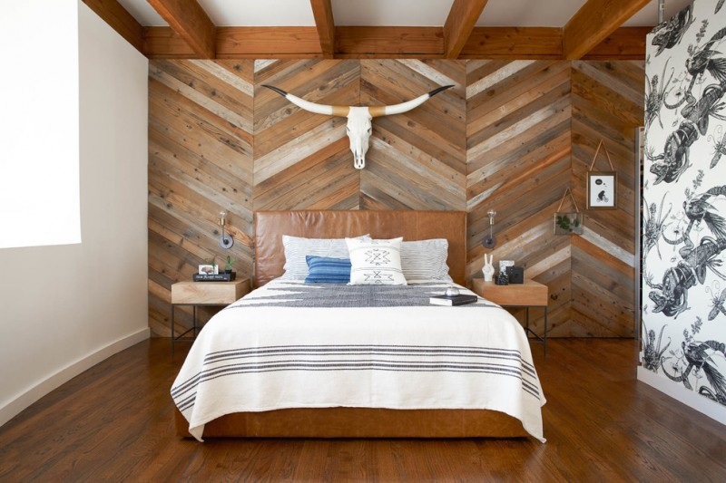 chevron accent wall wooden wall wooden floor wooden nightstand brown leathered bed wall sconces white bedding brown leathered headboard