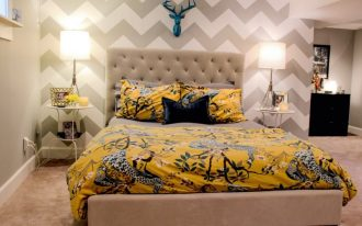 chevron accent wall yellow bedding beige bed tufted headboard side tables deer head table lamps black drawers window
