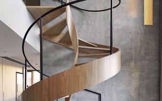 complicated spiral wooden stairs with black meta as handrails