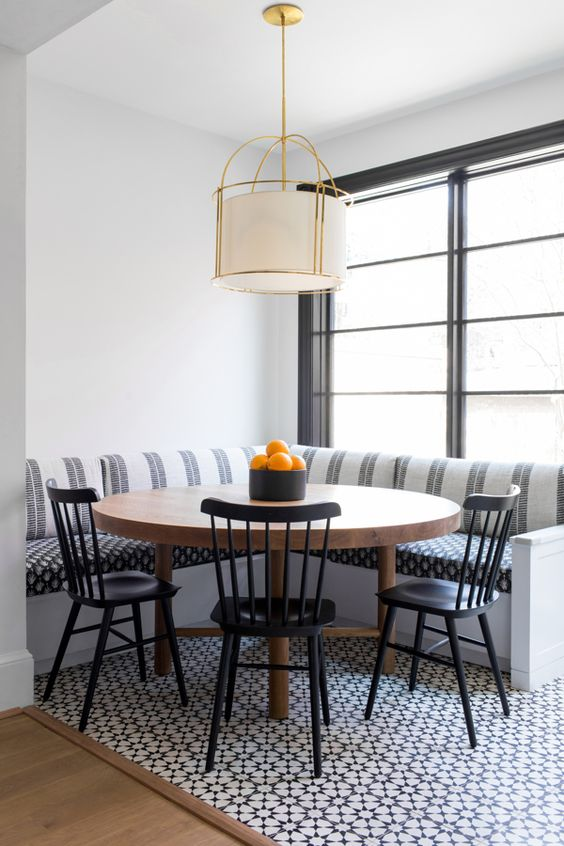 corner dining set with round wooden table, black metallic chair, striped corner bench