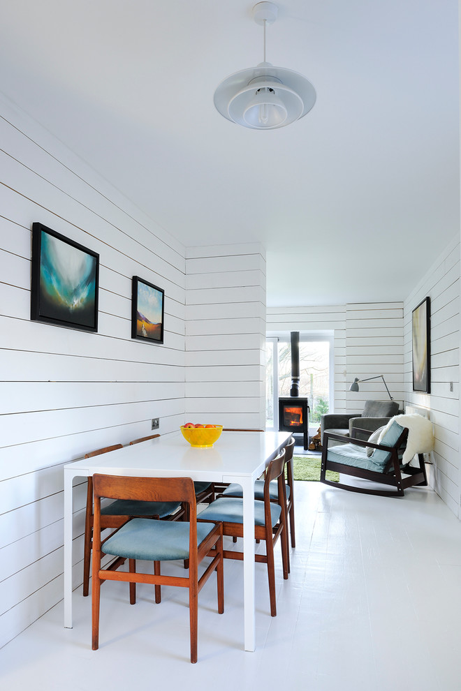 dining area in the hallways in an open white room with white floor, white striped wall, white square table, brown wooden chairs with blue cushion