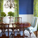 Dining Room With Grand Wooden Table And Chairs, Chandelier, Rug, Blue Wall, Green Plants Patterned Curtain