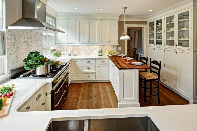 double pendant light white cabinets mosaic backsplash wooden floor black barstools wooden and white countertops stove range hood oven windows