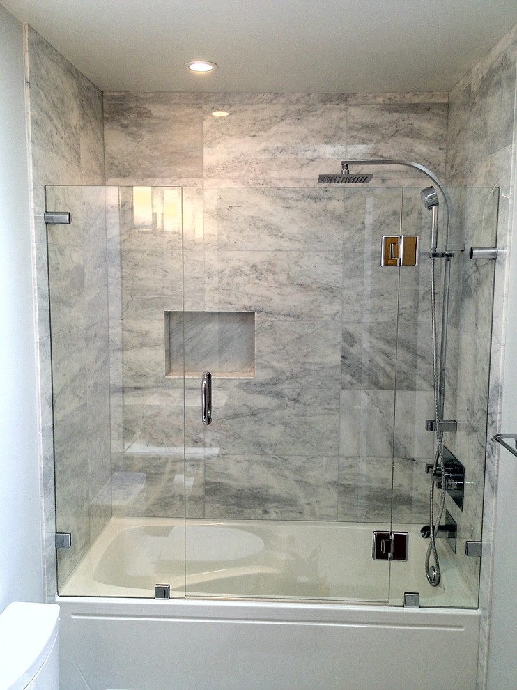 frameless hinged tub door black marble wall tle shower head shower fixture white built in shower white walls recessed lighting