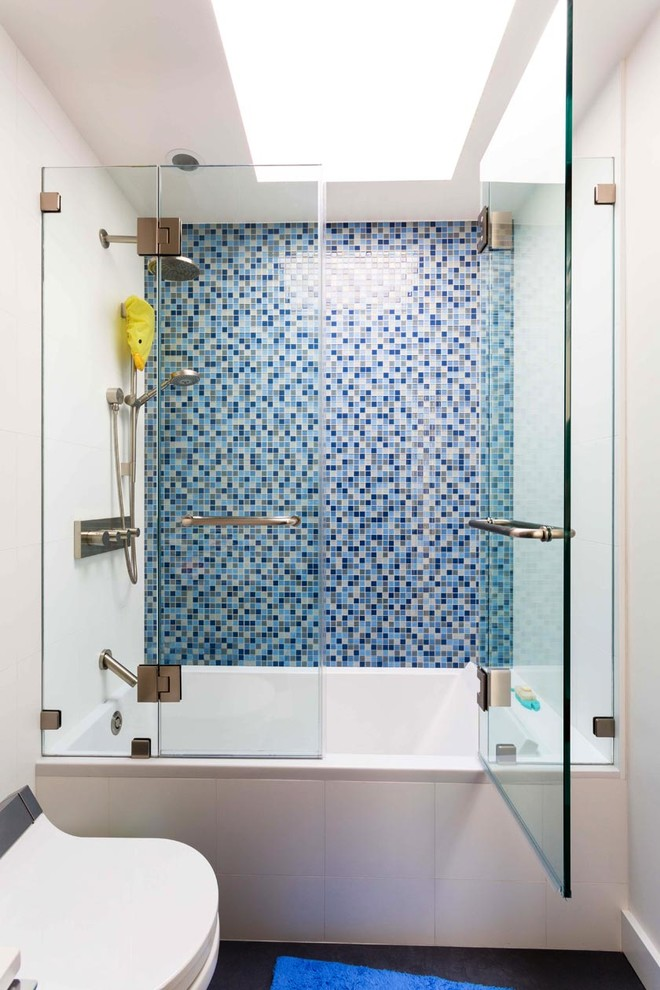 frameless hinged tub door blue mosaic wall tile shower head built in tub blue bathroom mat white walls brown floor